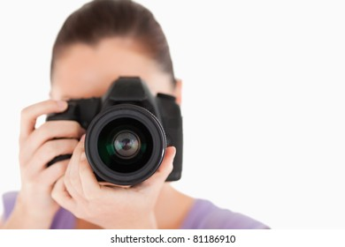 Good looking female using a camera while standing against a white background