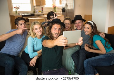 Good looking group of friends taking a selfie on a tablet are smiling