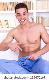 good looking guy in pajamas with naked chest pointing at his lower area