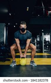 Good looking handsome male athlete with protective face mask exercising in modern fitness gym. Dark muddy light with strong shadows. Pandemic sports indoors concept.