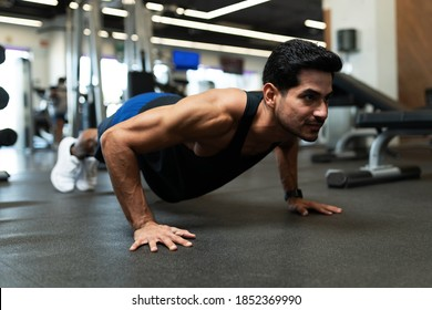 Good looking hispanic young man doing some push up exercises for his core muscles at the fitness center
