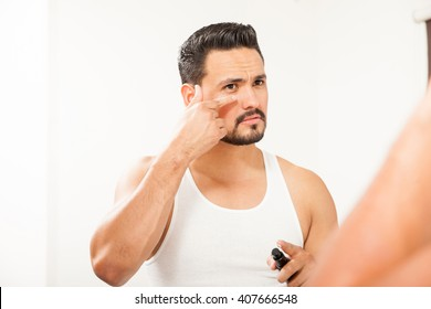 Good looking Hispanic young man putting on some anti-aging cream to prevent bags under eyes in the bathroom