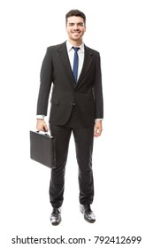 Good looking Hispanic young man in a suit carrying a briefcase and smiling in a studio
