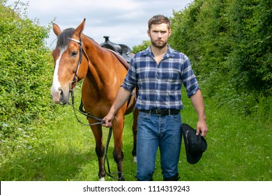 Good looking, hunky cowboy walking next to his horse, stallion with boots, chequered shirt and hat