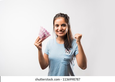 Good looking Indian / Asian girl holding money fan consisting of new 2000 rupee notes, isolated over white background
