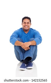 good looking indian man sitting on floor isolated on white background
