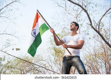 Good looking Indian young man holding / waving or running with indian tricolour flag outdoor near lake, conceptual image for republic day or independence day greeting card.