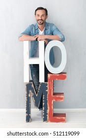 Good looking joyful man standing behind the letters HOME