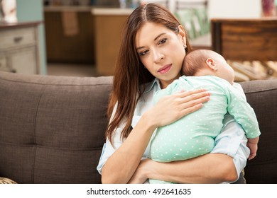 Good looking Latin woman sitting in a couch at home and holding her newborn baby in her arms