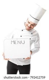 Good looking Latin young chef holding a sign with the menu and looking at it in a studio
