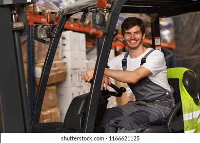 Good looking loader sitting in forklift, posing and smiling. Professional worker wearing uniform and white t shirt. Background of warehouse with many boxes and goods.