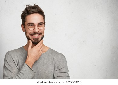 Good looking male with appealing smile has thoughtful cheerful expression, keeps hand under chin, plans how to spend lump sum of money which he earned, isolated over white background, copy space