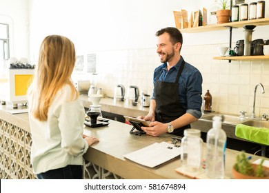 Good looking male barista taking an order from a customer with a tablet in a coffee shop and smiling