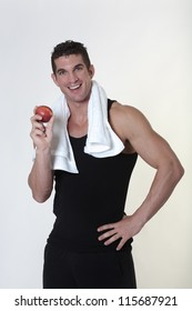 good looking male bodybuilder just done a work out with a towel around his neck about to eat a apple
