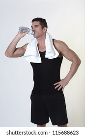 good looking male bodybuilder just done a work out with a towel around his neck drinking water