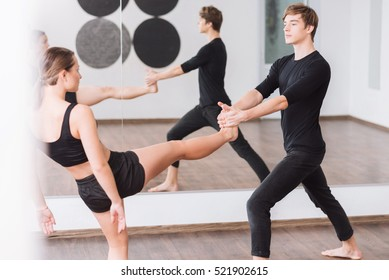 Good looking male dancer holding the leg of his partner