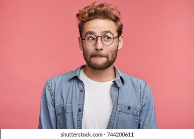 Good looking male model with stubble presses lips, looks pensively aside, thinks over his future actions or plans, wears spectacles, has clever expression, isolated over pink studio background