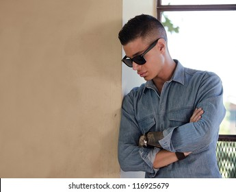 Good looking male model with sunglasses looking down, with large copy-space