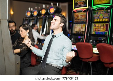 Good looking man celebrating he just won a lot of money in a slot machine at a casino