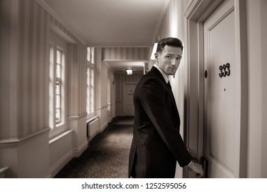 Good looking man in hotel corridor using key card to open room door