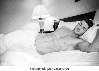 Good looking man with muscular body and six pack abs sleeping in between white sheets in hotel room