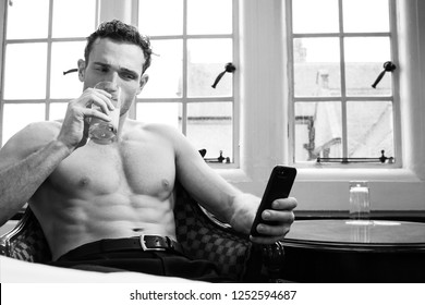 Good looking man with muscular pecs and six pack abs drinking juice while using mobile phone next to window