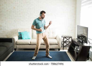 Good looking man practicing slow dancing by himself listening to music with headphones in the living room