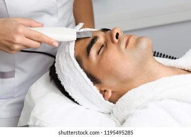Good looking man receiving ultrasound cavitation facial peeling. Skin cleansing procedure at beauty spa salon.