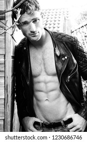 Good looking man with sixpack abs and leather jacket looking at camera