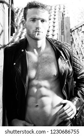 Good looking man with sixpack abs and leather jacket smoking a cigarette and looking at camera