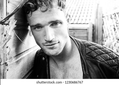 Good looking man with stubble and open jacket looking at camera