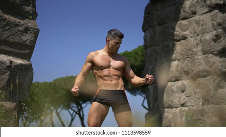 Good looking man wear unbuttoned shirt showing his great abs. Outdoor fashion and fitness shoot
