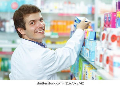 Good looking medical specialist in white coat and with chestnut hair posing. Positive male pharmacist smiling, looking at camera and taking some medicaments from shelf.