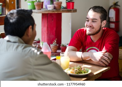 Good looking men having lunch in an outdoor restaurant, men chatting and smiling