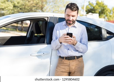 Good looking mid adult man text messaging on smartphone while standing next to his car