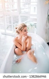 Good looking naked female with perfect skin, expressive eyes, plump lips, red manicure sitting in bathtub with white towel on head in modern spa salon. People, wellness and body care concept.