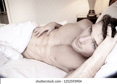 Good looking naked man with six pack abs and blue eyes eyes lying naked in bed