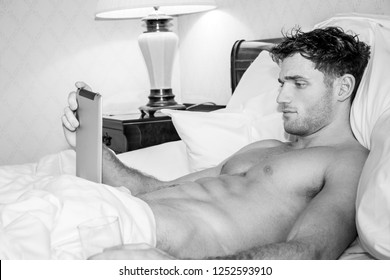 Good looking naked man with six pack abs lying in bed using digital tablet