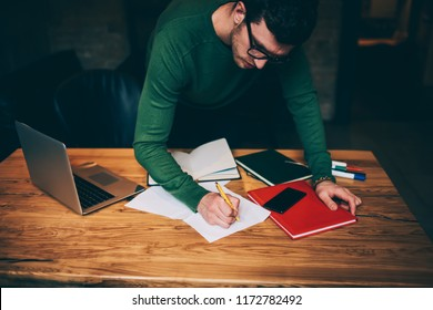 Good looking pensive caucasian employee carefully creating organisation plan during paper work, serious pondering architect writing main theses for startup project standing near wooden desktop