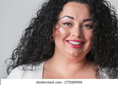 Good looking plus size model.Beautiful young woman in 30s with curly dark hair,red lipstick & makeup posing with cheerful toothy smile in studio.Attractive plump girl smiling friendly with white teeth