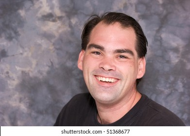 a good looking regular guy is looking directly at viewer with a big toothy smile