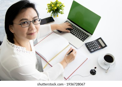 Good looking senior Asian businesswoman sitting at desk and working with notebook computer and cup of coffee.