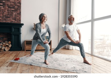 Good looking senior couple in sports clothing exercising and smiling while spending time at home