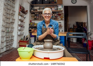 Good looking senior female potter working on pottery wheel while sitting  in her workshop