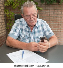 Good looking Senior searching in his mobile phone in his backyard