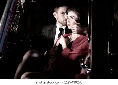 Good looking sexy couple, handsome man in suit, beatiful woman in red dress, touching, holding each other passionately in vintage car