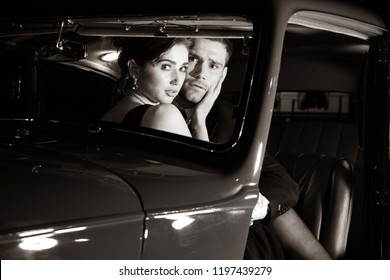 Good looking sexy couple, handsome man in suit, beatiful woman in red dress, are caught by paparazzi photographer in vintage car