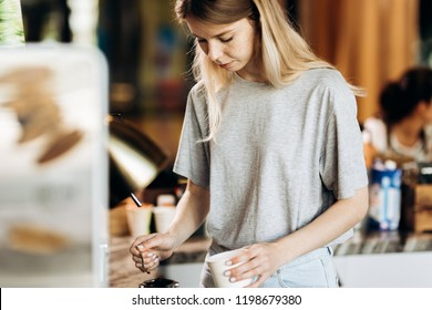 A good looking slim blonde with long hair,dressed in casual outfit,is cooking coffee in a modern coffee shop. Process of making coffee is shown.
