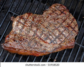 Good looking steak cooking on open grill