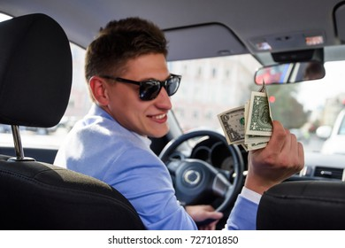 Good looking taxi driver gives change to a client. The payment in the taxi concept. Honest client-oriented policies.